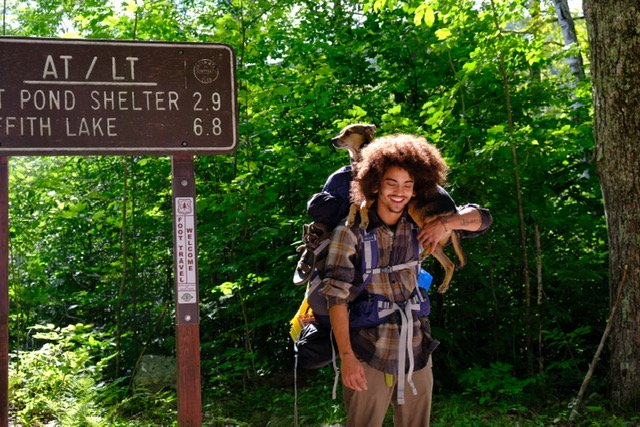 Raei stands next to the long trail/Appalachian trail sign with dog companion Rex on his shoulders
